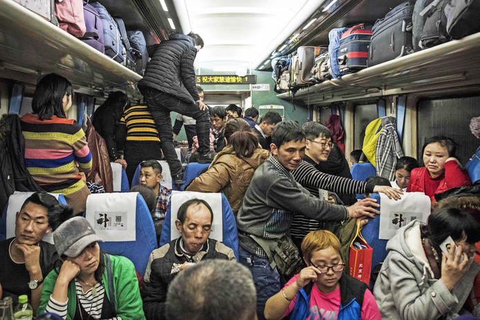Chinese passagiers reizen in een overvolle trein, in een rit van 26 uur, van Beijing naar Chengdu. Ze gaan thuis bij familie het lentefeest vieren. Foto Fred Dufour