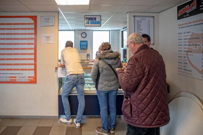 In de rij bij het eetloket van voetbalvereniging Alphia. Er zijn wat varianten broodjes gezond te krijgen, maar vooral aan gefrituurde lekkernijen is geen gebrek.
