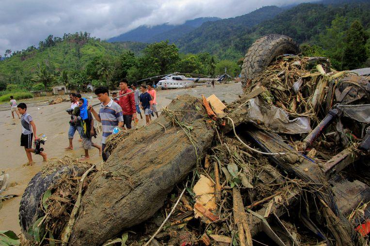 Mensen lopen langs een beschadigde auto in Sentani, op Papoea. Beeld REUTERS