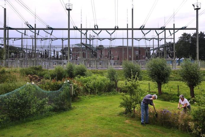 Peter van Beek en Francis Akkermans werken in hun tuin pal naast het Bredase 150kV-station. foto ramon mangold/pix4profs