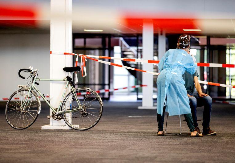 Een medewerker van de GGD Utrecht neemt een coronatest af in een teststraat in Houten. Beeld ANP
