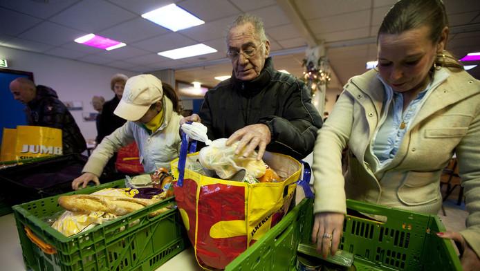 Bezoekers halen voedselpakketten op voor de kerstdagen in de Morgensterkerk in Den Haag.