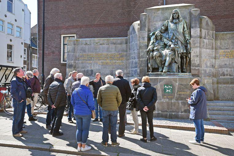 Nederlandse toeristen laten zich door een gids bijpraten over de Dordtse geschiedenis bij het beeld van de Gebroeders de Witt.  Beeld null
