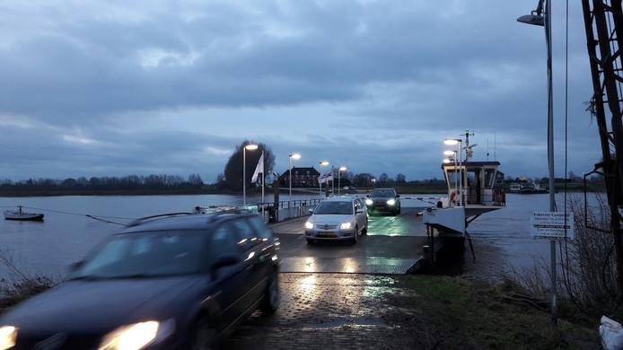 Auto's rijden van het Opheusdense veer af.  Het kan nog net, ondanks het opkomend hoogwater.