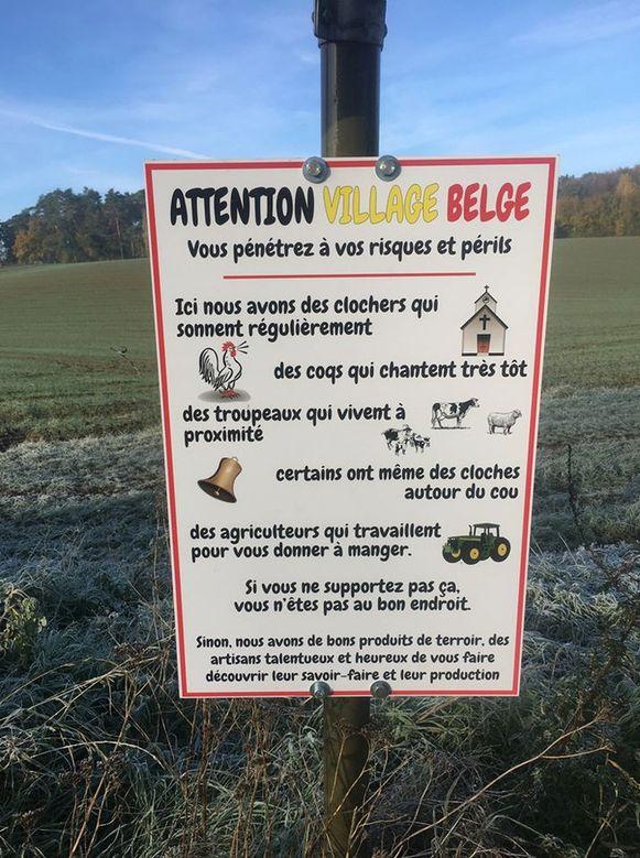 Een ludiek bord om mensen duidelijk te maken dat ze op eigen risico een Belgisch dorp betreden.