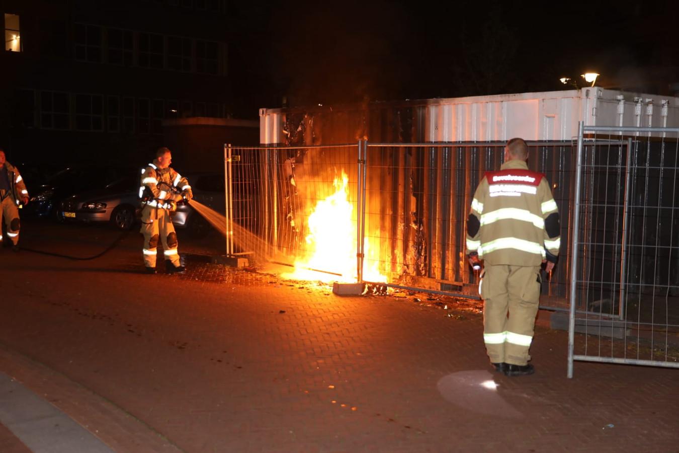 Brandweermannen blussen de brandende jerrycans.