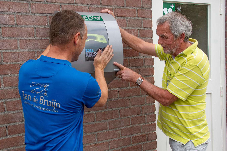 De nieuwe AED in Haghorst wordt geplaatst.