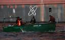 Een vissersbootje passeert de drijvende kerncentrale.
