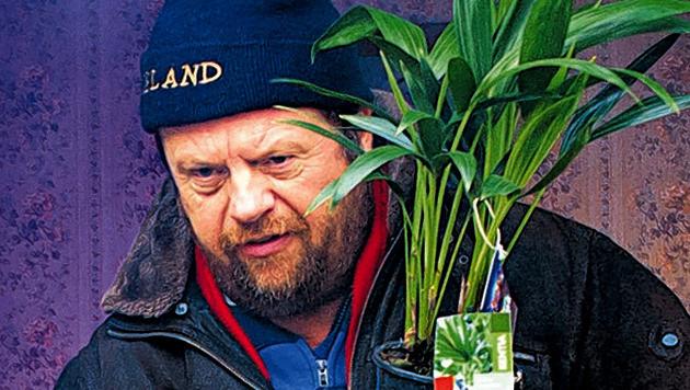 De gevallen PvdA-politicus maakt zich zo snel mogelijk uit de voeten en poogt zijn gezicht achter het plantje te verbergen.