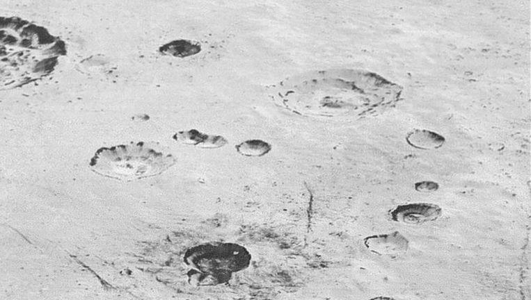 Gelaagde kraters en ijzige vlakten op Pluto. Beeld NASA/JHUAPL/SwRI
