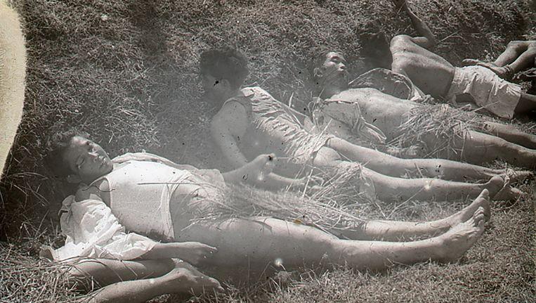 Zes lichamen van Indonesiërs. De mannen zijn neergeschoten, hun ontklede onderlichamen zijn met stro bedekt. Beeld .