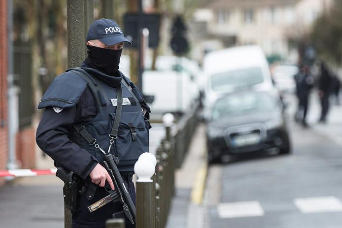 Een agent houdt de wacht bij het appartementencomplex in Argenteuil, waar diverse vuurwapens en explosieven werden gevonden