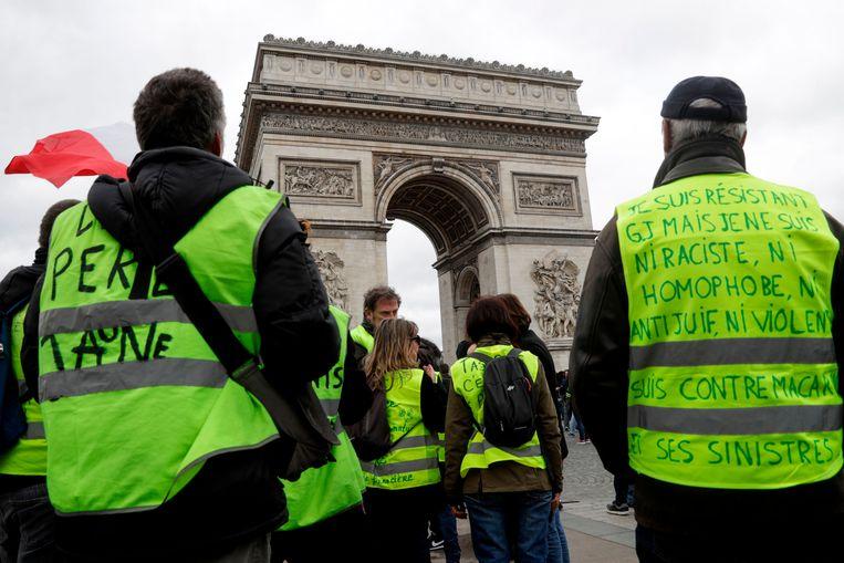Enkele gele hesjes verzamelen voor de achttiende zaterdag op rij aan de Champs Elysées.