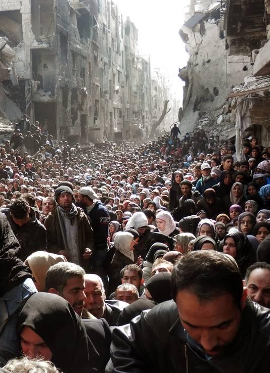 Mensen stromen samen in een verwoeste straat, wachtend op noodhulp.