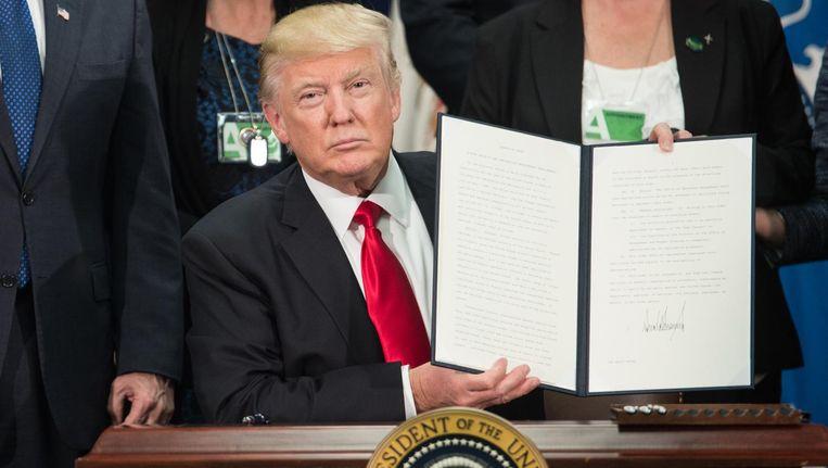 Donald Trump met het ondertekende uitvoeringsbevel om te beginnen met de bouw van de muur op de grens met Mexico. Beeld AFP