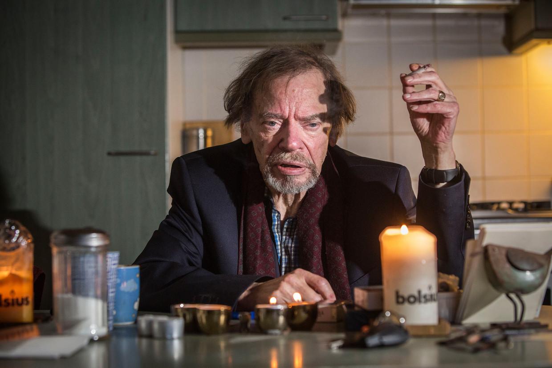 Wessel te Gussinklo aan de keukentafel waar hij in een schriftje zijn verhalen schrijft, bij kaarslicht.
