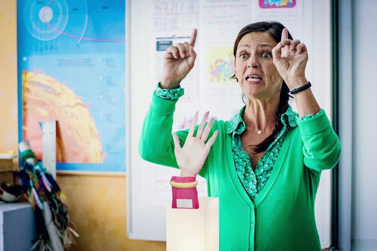De Vlaamse juf Ank, juf Els (gespeeld door Els Dottermans) demonstreert een 'zwaailicht' voor de ouders - waarmee wordt aangegeven wanneer ze naar hun kinderen mogen zwaaien.  Beeld VTM
