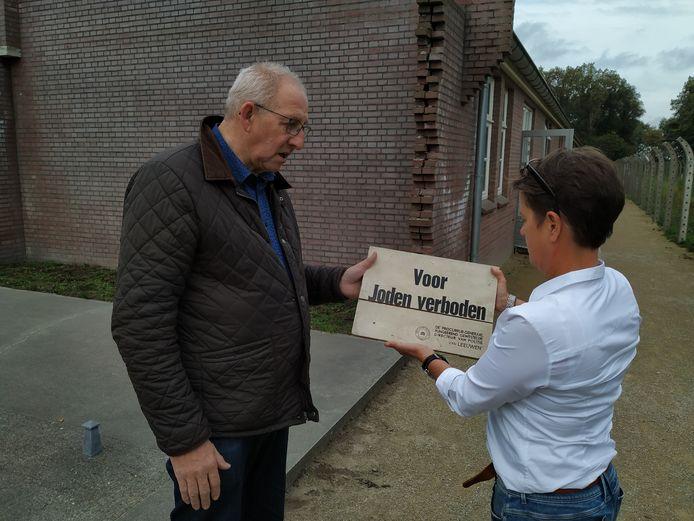 Gerard van der Linden, voorzitter van Berchs Heem, overhandigt het bordje aan Brigitte Kok van Kamp Vught.