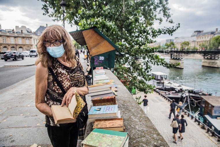 Bouquiniste Michelle controleert haar boeken. De intellectuele toerist laat het afweten, waardoor de boekverkopers het zwaar hebben.  Beeld Aurélie Geurts