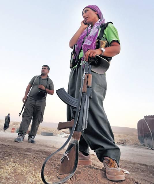 Een met een kalasjnikov uitgeruste vrouw krijgt instructies via haar mobiele telefoon.