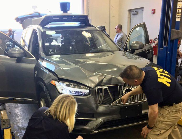 Medewerkers van de National Transportation Safety Board onderzoeken de auto van Uber waarmee het ongeluk gebeurde.