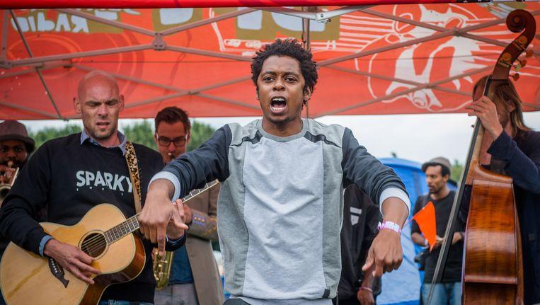 Rapper Typhoon (Glenn de Randamie, midden) geeft een optreden op de 3FM minicamping op de derde en laatste dag van de 22e editie van muziekfestival Lowlands. Beeld ANP Kippa