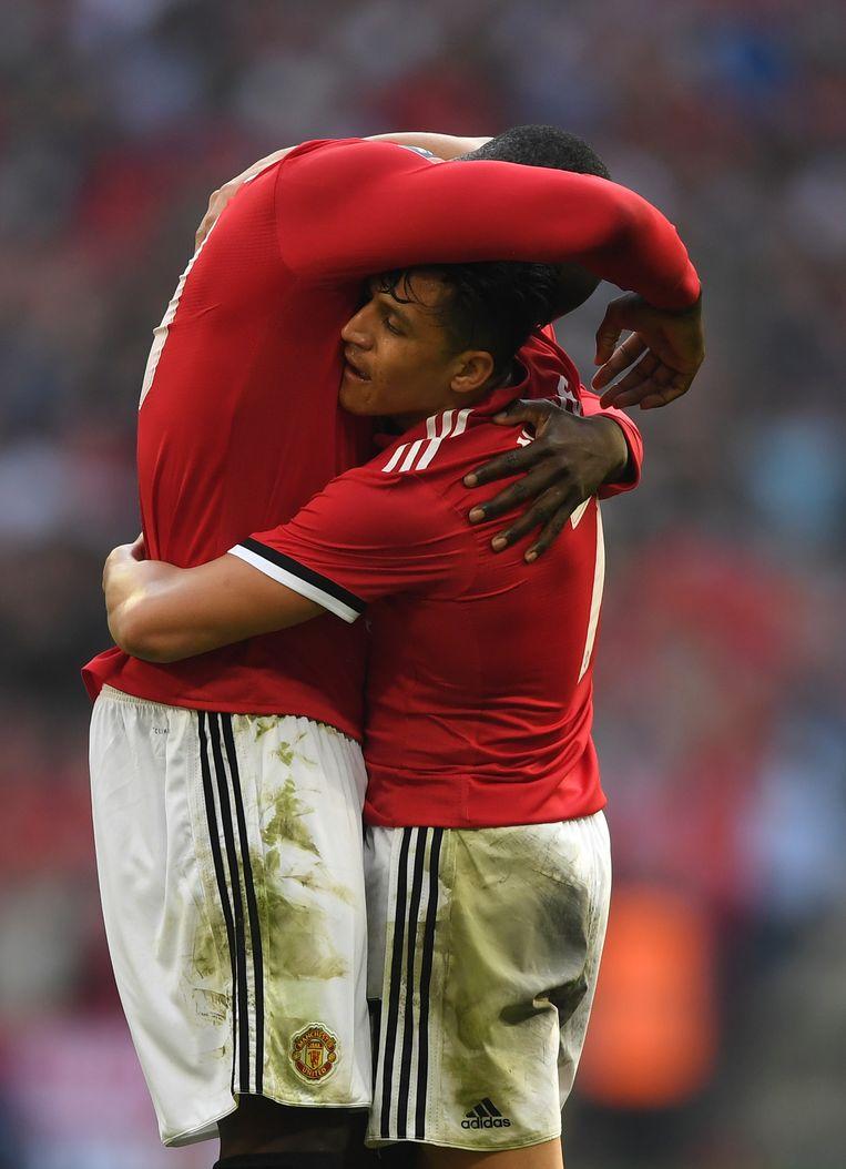 Lukaku in de armen van Sanchez.