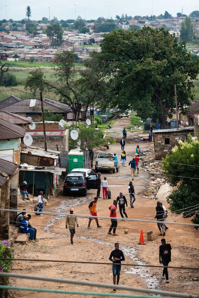 Voor een land in lockdown is het opvallend druk in de straten van sloppenwijk Freedom Charter in het Zuid-Afrikaanse township Soweto. Beeld Bram Lammers