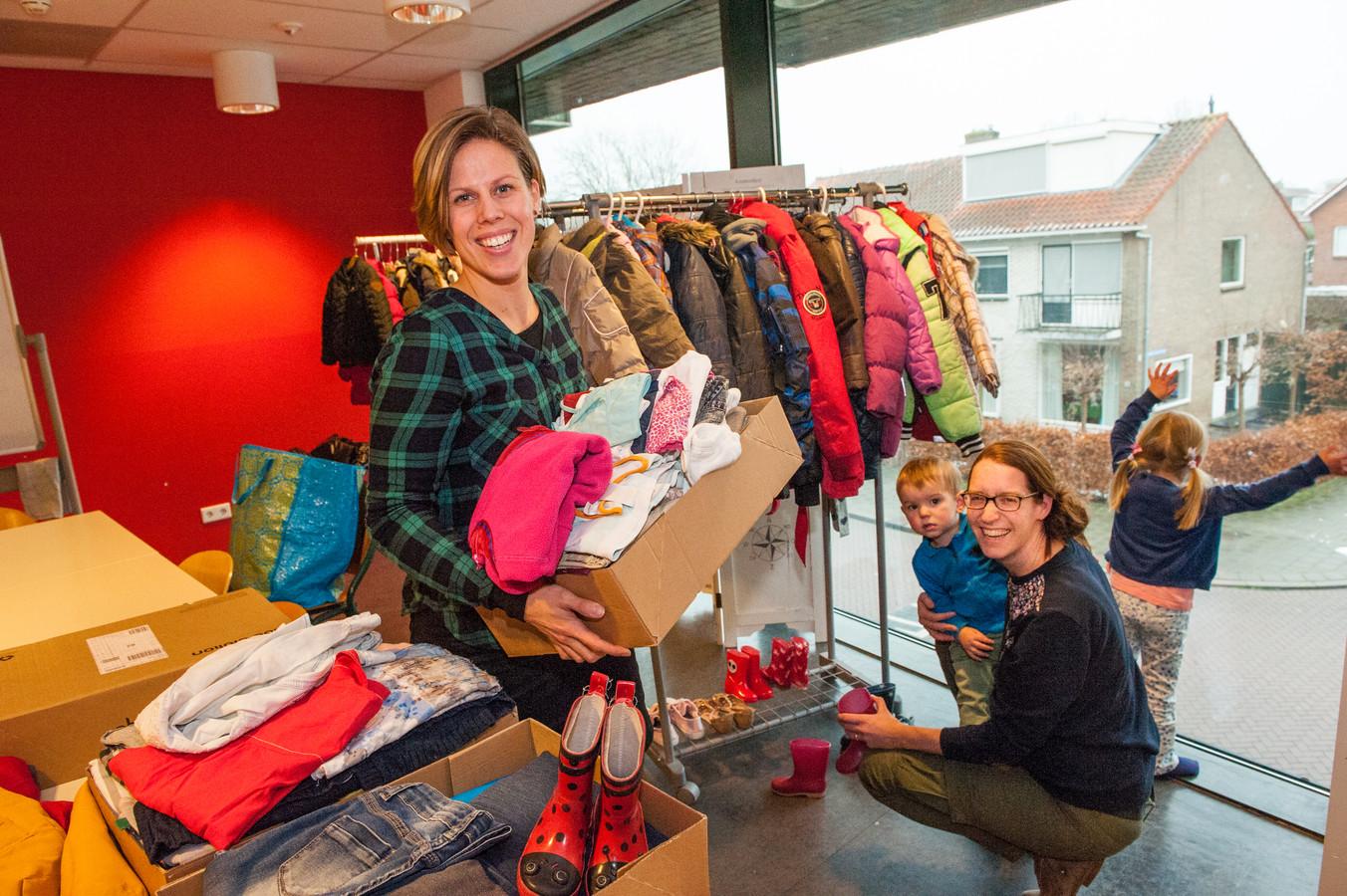 Roos Bonnier en vrijwilligster Roeliene selecteren kledig en schoeisel in het kinderkledingruilpunt Krijgdekleertjes.