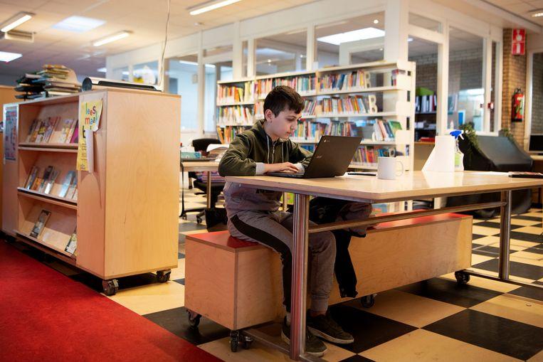 Efe (12) maakt huiswerk in de hal van basisschool Wereldwijs in de Amsterdamse Bijlmer. De school vangt kwetsbare zorgleerlingen op. Beeld Olaf Kraak