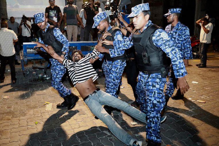 Een betoger wordt meegenomen door de politie.