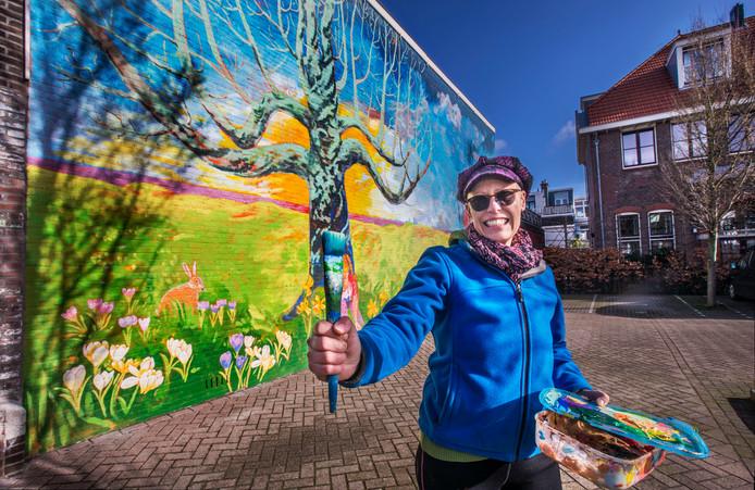 Margriet Snaterse maakt een muurschildering in de Meidoornstraat.