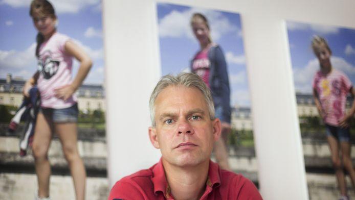 Peter van der Meer met op de achtergrond de grote foto's die hij van zijn dochters maakte tijdens hun vakantie in Parijs.
