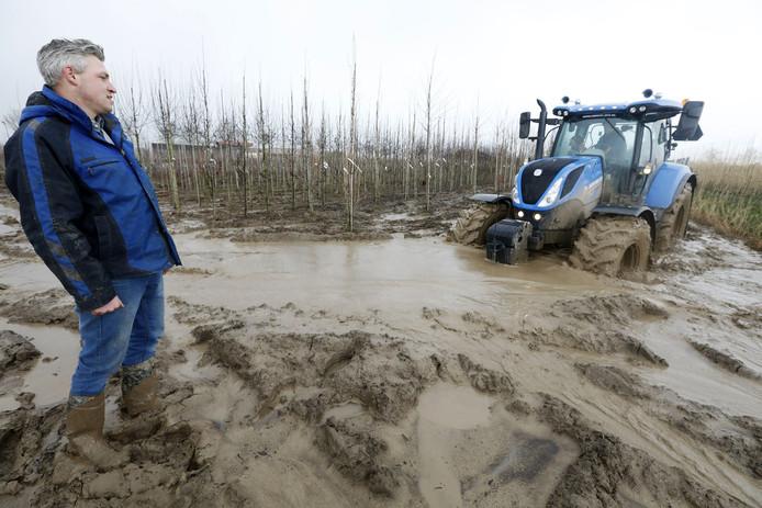 Bram de Greef van Betuwe Boomkwekerij kijkt hoe een collega de tractor door de klei probeert te sturen.