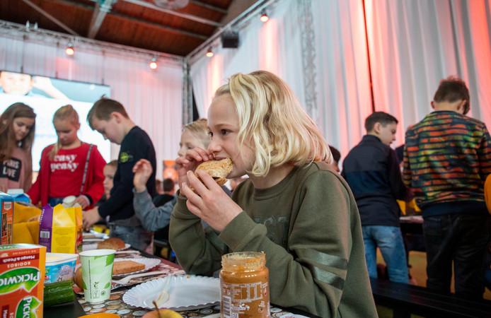 Een Edes schoolmeisje neemt een hap in haar broodje tijdens het schoolontbijt in de Mauritskazerne in Ede.