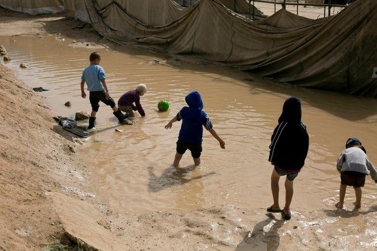 Kinderen spelen in een modderpoel bij het Al Hol-kamp in de Koerdische regio in Syrië. Beeld AP