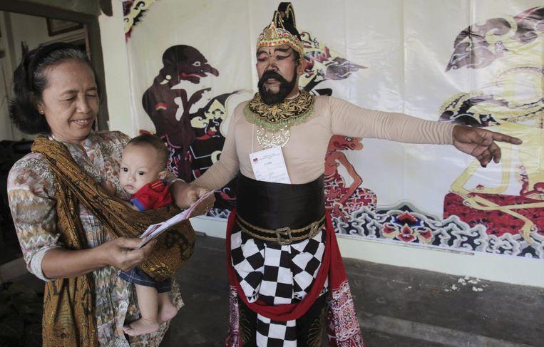 Een man in theatraal kostuum wijst een kiezer de weg naar een stembureau in Surakarta. Beeld reuters