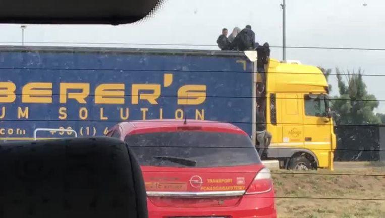 Een getuige kon deze beelden maken van een groep transmigranten die in een vrachtwagen proberen te klauteren op de snelwegparking in Kruibeke.