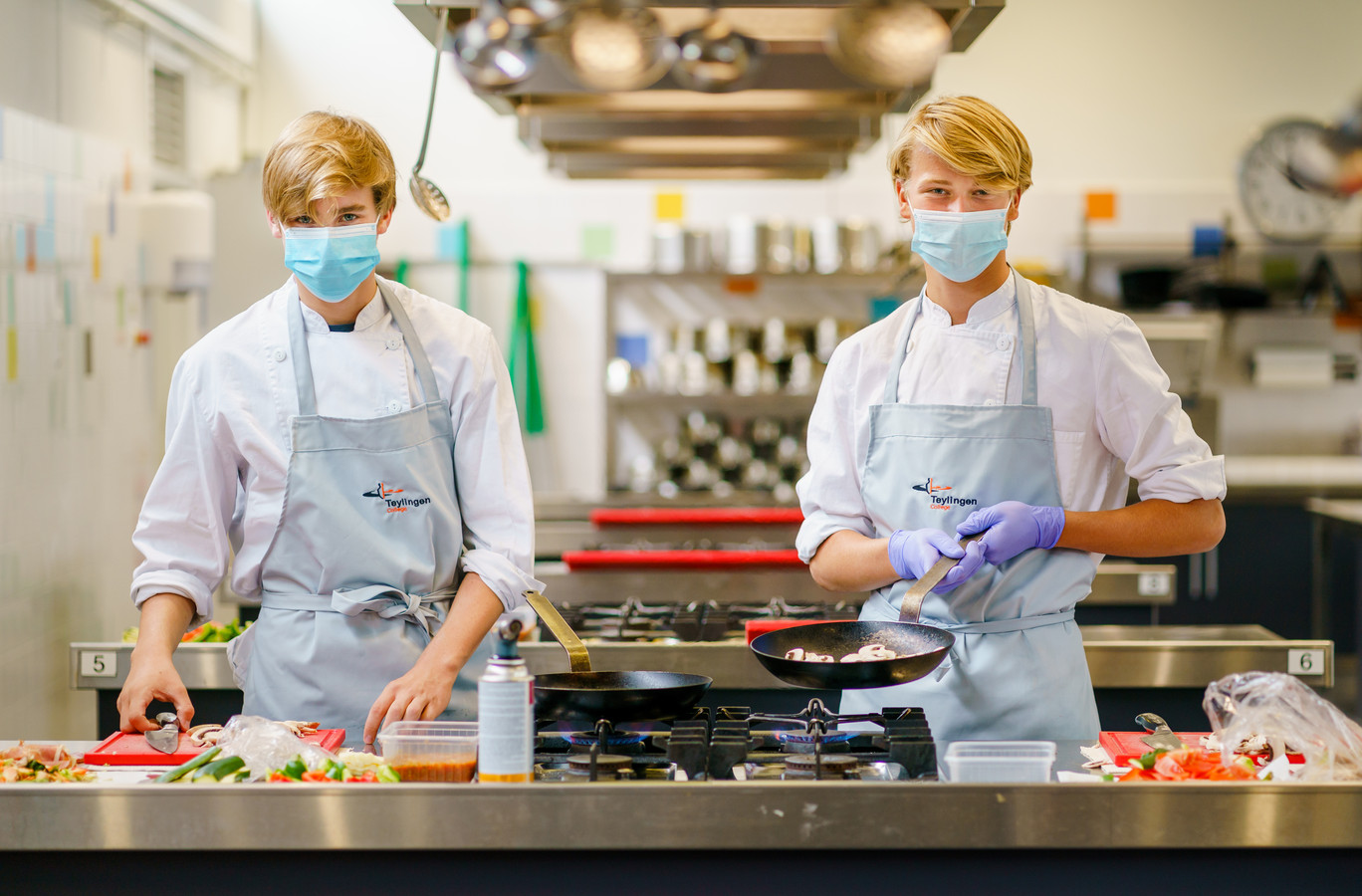 Sven Beekman (l) en Michiel Gravesteijn volgen het keuzevak traiteur en leren professionele maaltijden bereiden. Tijdens de lessen is een mondkapje verplicht.