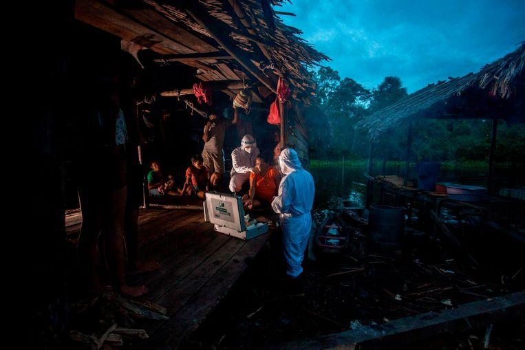 Zorgmedewerkers uit de stad Melgaco onderzoeken begin juni een vrouw met coronaverschijnselen uit een kleine dorpsgemeenschap op het eiland Marajó in Noord-Brazilië. Beeld Tarso Sarraf / AFP