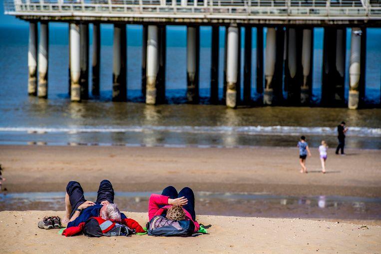 Bezoekers liggen te zonnen op het Scheveningse strand. Beeld null