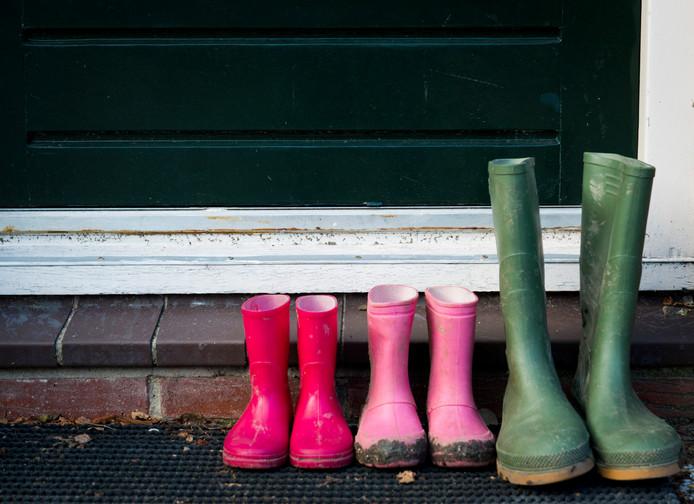 Regenlaarzen van een gezin bij de voordeur.