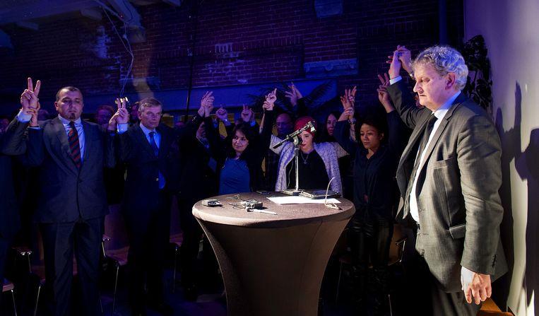 Burgemeester Eberhard van der Laan van Amsterdam en de andere aanwezigen houden elkaars hand vast tijdens een minuut stilte. Enkele honderden joden en moslims kwamen bijeen om stil te staan bij de terreurdaden in Parijs Beeld null