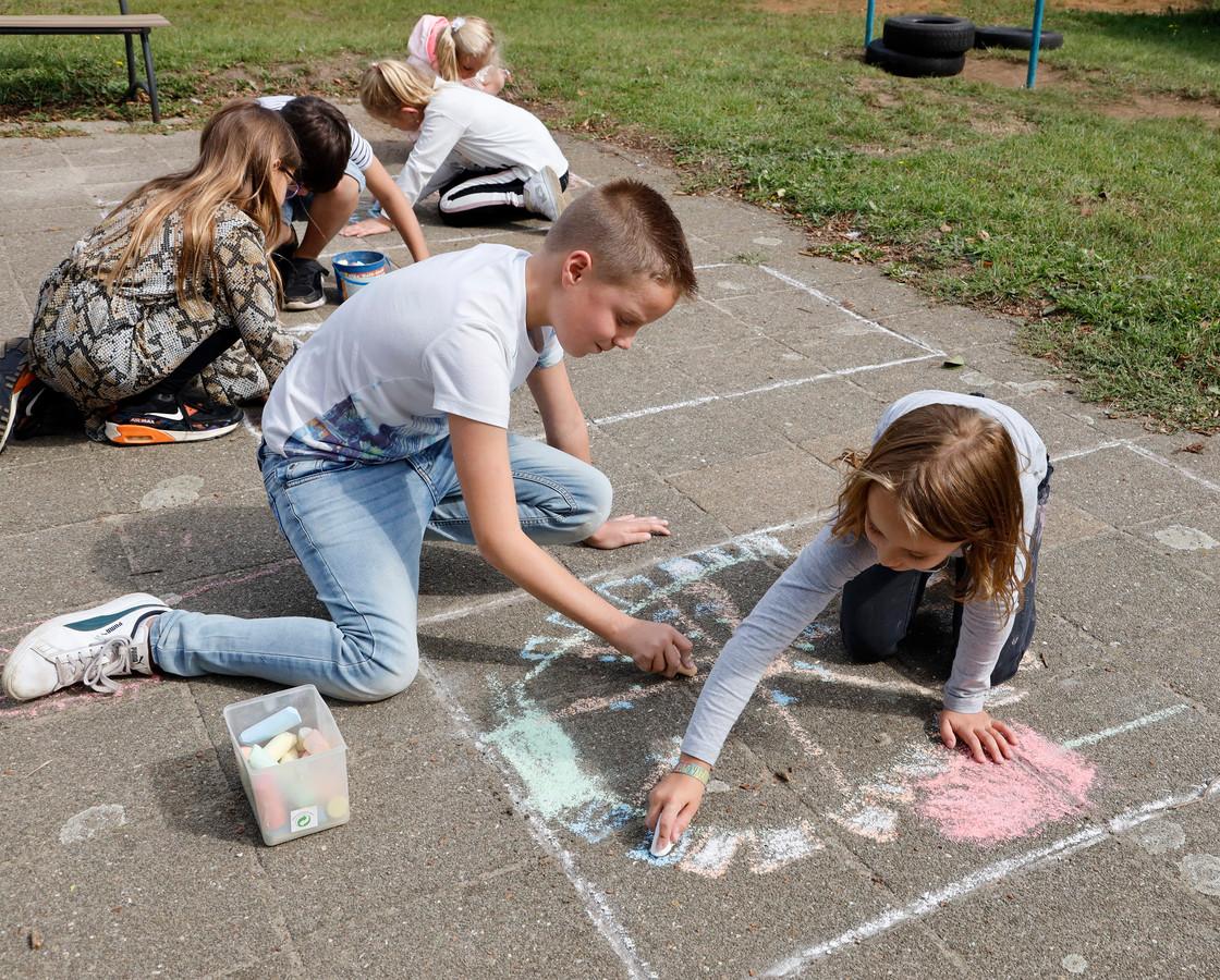 Senne (links) en Summer van basisschool Sint Jozef  uit Nieuw Namen tekenen een reuzenrad met stoepkrijt