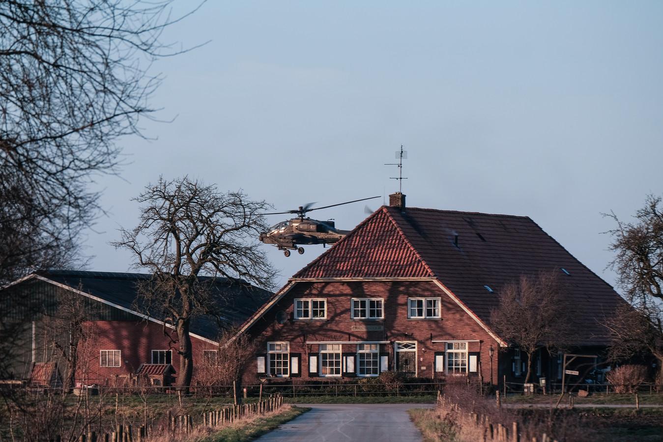 Een helikopter vliegt laag boven een Achterhoekse boerderij.