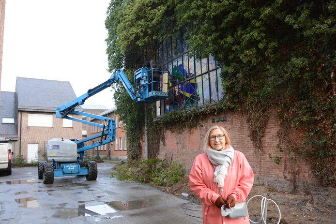 Ann Cools bij het monumentale glasraam dat half verscholen zat onder de klimop.