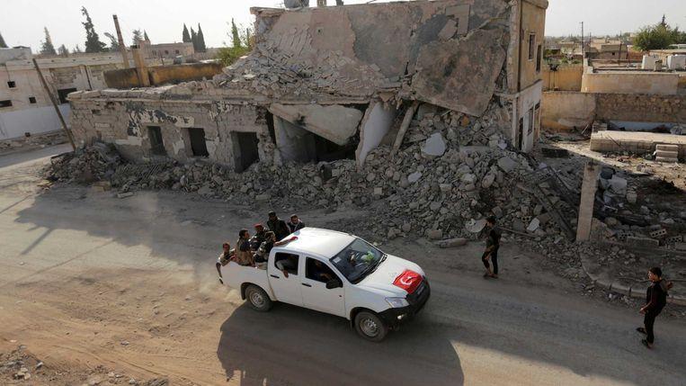 Strijders van het Vrije Syrische Leger in een pick-up truck met een Turkse vlag rijden langs kapotte gebouwen in het noord-Syrische al-Rai, in de regio Aleppo. Beeld Reuters