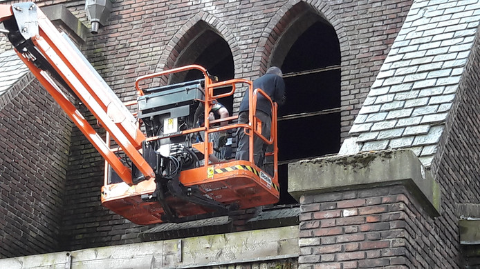 Medewerkers van Hagemeier zijn woensdag bezig de glas-in-loodramen te demonteren.