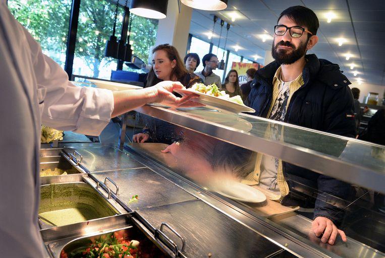 Een student krijgt zijn maaltijd in de kantine van de Radboud Universiteit. Beeld null