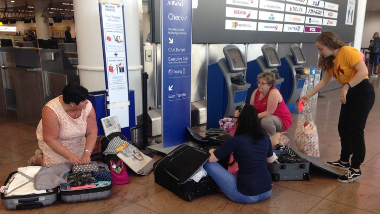 Veel reizigers herschikken vlug nog hun bagage in de vertrekhal nadat opgeroepen werd om enkel met handbagage te reizen.